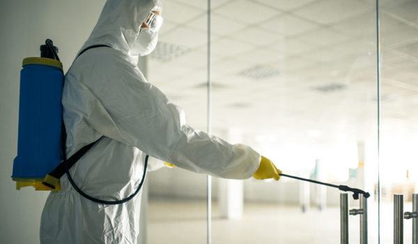 Sanitary worker sprays an empty business center with antiseptical liquid to prevent covid-19 spread. A man wearing disinfection suit cleaning up the shopping mall. Nobody, health, isolated concept.